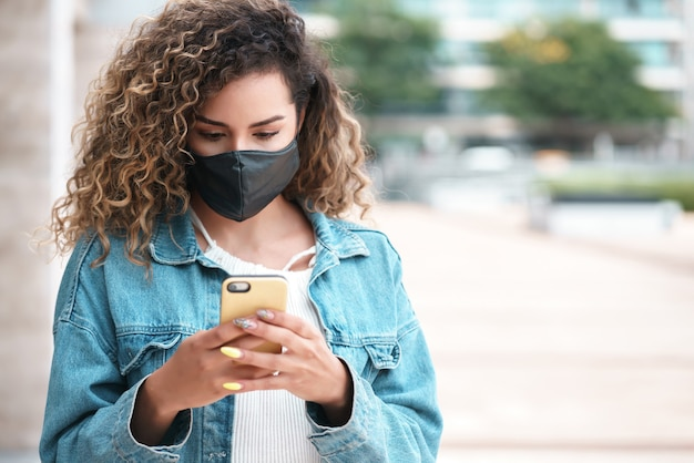 Young latin woman wearing a face mask while using her mobile phone outdoors in the street. new normal lifestyle. urban concept.