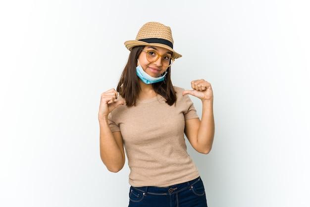 흰색에 고립 된 covid로부터 보호하기 위해 모자와 마스크를 착용하는 젊은 라틴 여성은 자랑스럽고 자신감을 느낍니다.
