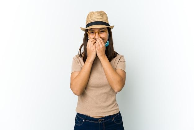 뭔가에 대해 웃고, 손으로 입을 덮고 화이트 절연 covid로부터 보호하기 위해 모자와 마스크를 착용하는 젊은 라틴 여자.