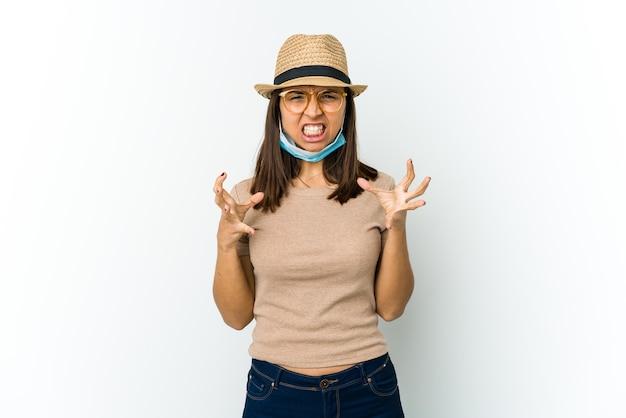 Молодая латинская женщина в шляпе и маске для защиты от covid изолирована на белой стене расстроена и кричит напряженными руками