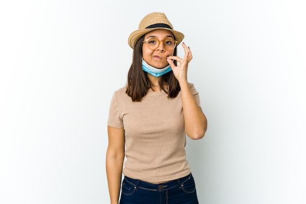 비밀을 유지하는 입술에 손가락으로 흰색 절연 covid로부터 보호하기 위해 모자와 마스크를 착용하는 젊은 라틴 여자.