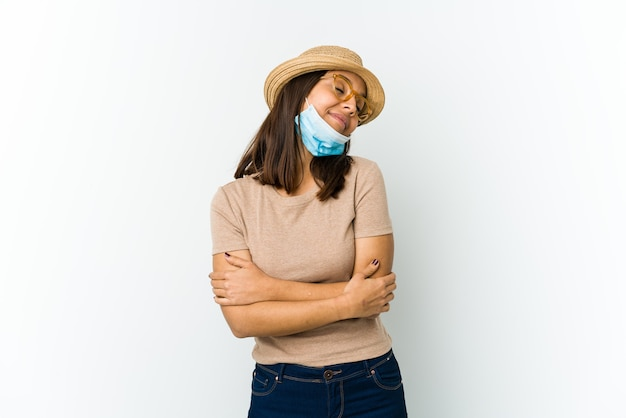 Young latin woman wearing hat and mask to protect from covid hugs, smiling carefree and happy.