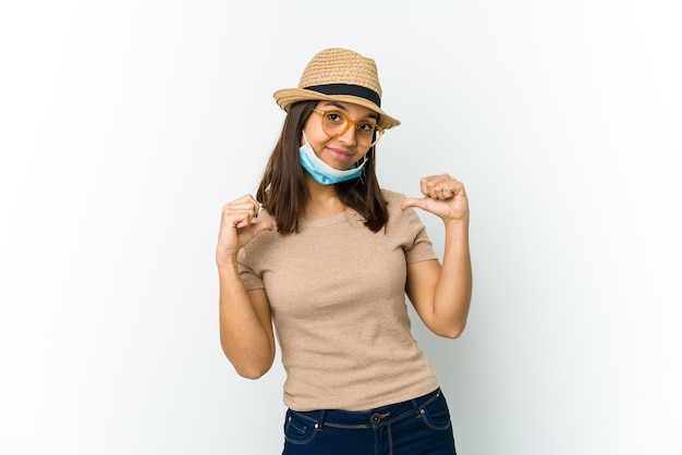 Young latin woman wearing hat and mask to protect from covid isolated on white feels proud and self confident, example to follow.