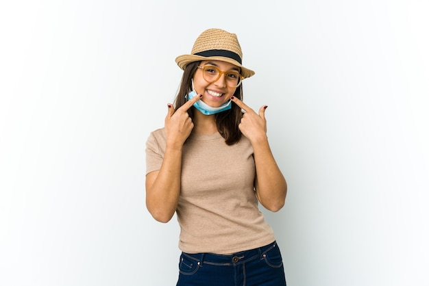Young latin woman wearing hat and mask to protect from covid isolated on white,  smiles, pointing fingers at mouth.