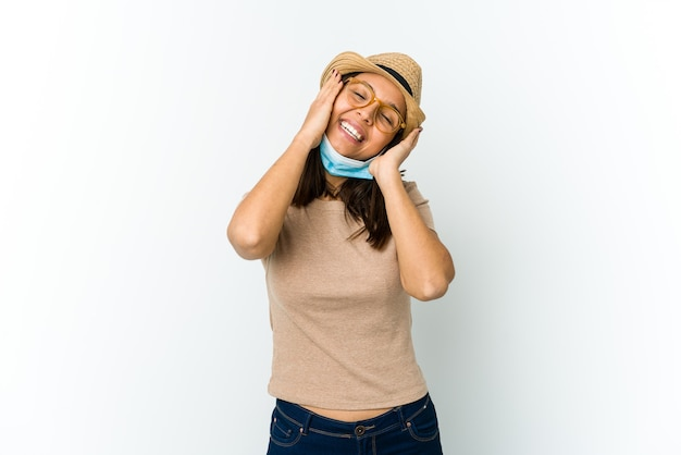 Young latin woman wearing hat and mask to protect from covid isolated on white wall laughs joyfully keeping hands on head. happiness concept.