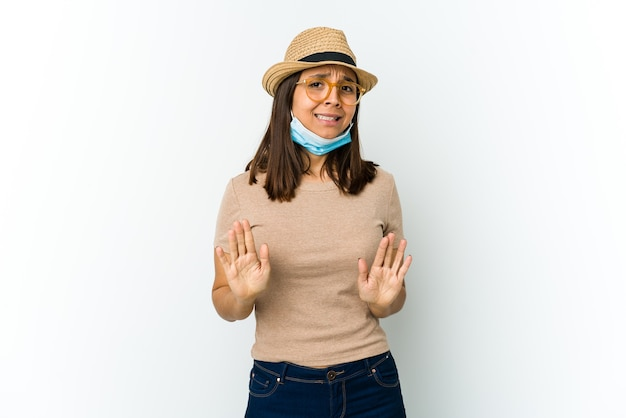 Young latin woman wearing hat and mask to protect from covid isolated on white wall rejecting someone showing a gesture of disgust.