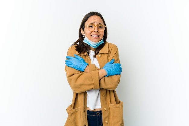 Young latin woman wearing a mask to protect from covid isolated on white wall going cold due to low temperature or a sickness.