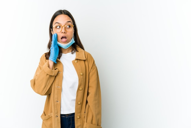 Young latin woman wearing a mask to protect from covid isolated on white wall is saying a secret hot braking news and looking aside