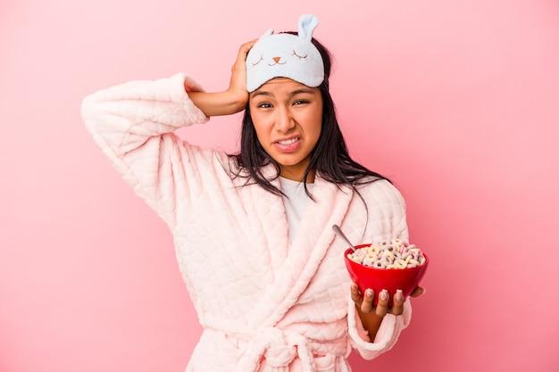 ピンクの背景で隔離されたシリアルのボウルを持ってパジャマを着ている若いラテン女性はショックを受けて、彼女は重要な会議を思い出しました。