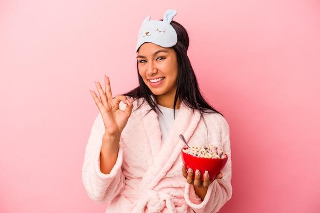 ピンクの背景に分離されたシリアルのボウルを保持しているパジャマを着ている若いラテン女性は陽気で自信を持って大丈夫なジェスチャーを示しています。