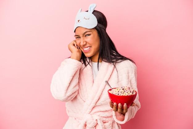 手で耳を覆うピンクの背景に分離されたシリアルのボウルを保持しているパジャマを着ている若いラテン女性。