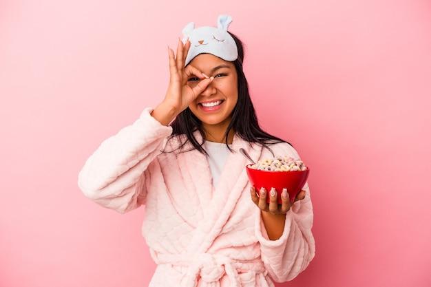 ピンクの背景に分離されたシリアルのボウルを保持しているパジャマを着ている若いラテン女性は、目に大丈夫なジェスチャーを維持して興奮しました。
