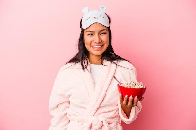 ピンクの背景に分離されたシリアルのボウルを保持しているパジャマを着て幸せ、笑顔、陽気な若いラテン女性。
