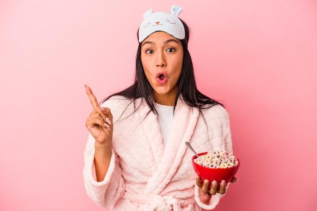 アイデア、インスピレーションのコンセプトを持つピンクの背景に分離されたシリアルのボウルを保持しているパジャマを着ている若いラテン女性。