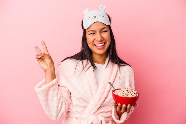 ピンクの背景に分離されたシリアルのボウルを持ってパジャマを着ている若いラテン女性は、指で平和のシンボルを示して楽しくてのんきです。