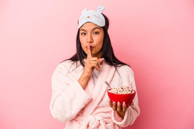 秘密を保持するか、沈黙を求めてピンクの背景に分離されたシリアルのボウルを保持しているパジャマを着ている若いラテン女性。