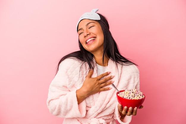 ピンクの背景に分離されたシリアルのボウルを保持しているパジャマを着ている若いラテン女性は、胸に手を置いて大声で笑います。