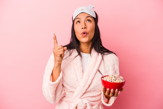 口を開けて逆さまを指しているピンクの背景に分離されたシリアルのボウルを保持しているパジャマを着ている若いラテン女性。