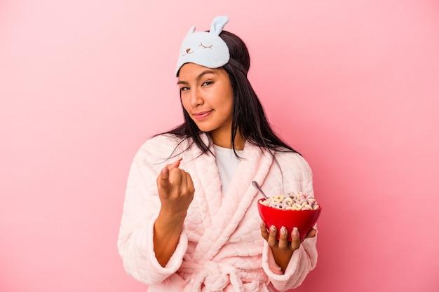 ピンクの背景に隔離されたシリアルのボウルを持ってパジャマを着ている若いラテン女性は、招待が近づくようにあなたに指を指しています。