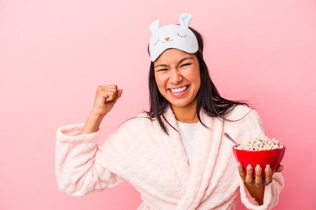 勝利、勝者の概念の後に拳を上げるピンクの背景に分離されたシリアルのボウルを保持しているパジャマを着ている若いラテン女性。