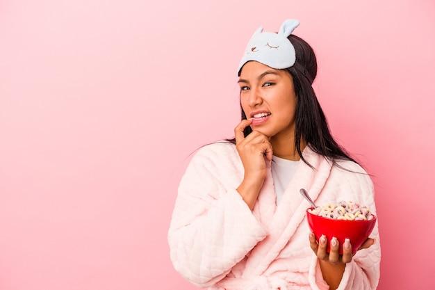 ピンクの背景に分離されたシリアルのボウルを保持しているパジャマを着ている若いラテン女性は、コピースペースを見ている何かについて考えてリラックスしました。