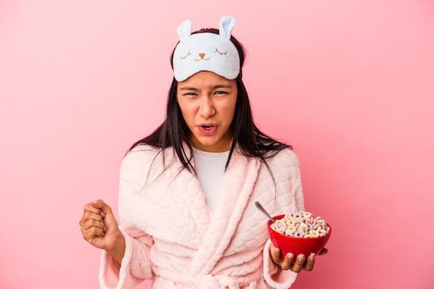 非常に怒って攻撃的な叫び声ピンクの背景に分離されたシリアルのボウルを保持しているパジャマを着ている若いラテン女性。