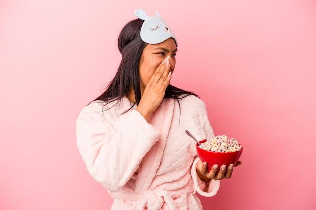 ピンクの背景に分離されたシリアルのボウルを持って叫び、開いた口の近くで手のひらを保持しているパジャマを着ている若いラテン女性。