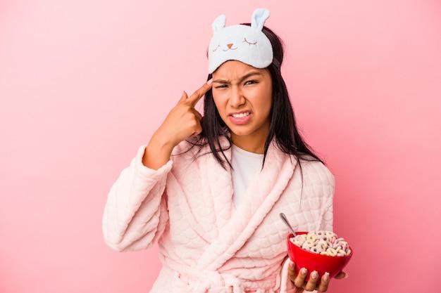 ピンクの背景に分離されたシリアルのボウルを保持しているパジャマを着ている若いラテン女性は、人差し指で失望のジェスチャーを示しています。