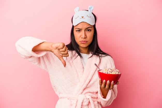 嫌いなジェスチャーを示すピンクの背景に分離されたシリアルのボウルを保持しているパジャマを着ている若いラテン女性は、親指を下に向けます。不一致の概念。
