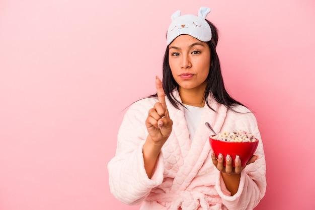指でナンバーワンを示すピンクの背景に分離されたシリアルのボウルを保持しているパジャマを着ている若いラテン女性。
