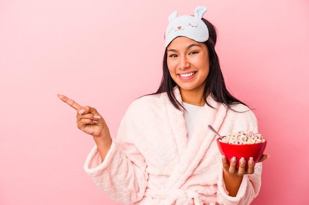 ピンクの背景に分離されたシリアルのボウルを持ってパジャマを着ている若いラテン女性は笑顔で脇を指して、空白のスペースで何かを示しています。