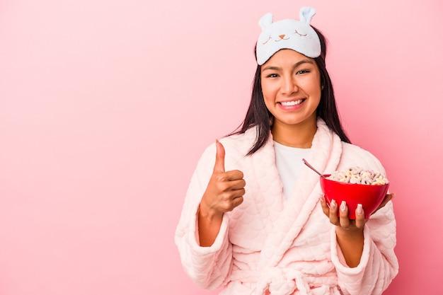 ピンクの背景に分離されたシリアルのボウルを持ってパジャマを着て笑顔と親指を上げて若いラテン女性