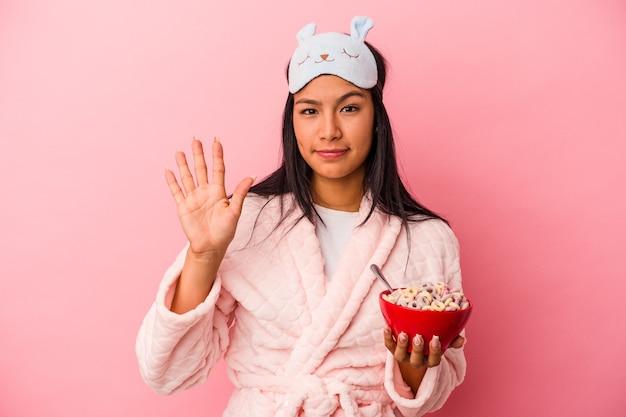 ピンクの背景に分離されたシリアルのボウルを保持しているパジャマを着ている若いラテン女性は、指で5番目を示す陽気な笑顔を浮かべています。