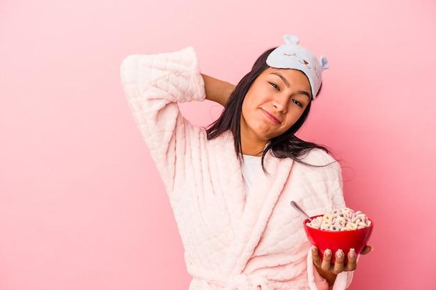 頭の後ろに触れて、考えて、選択をするピンクの背景に分離されたシリアルのボウルを保持しているパジャマを着ている若いラテン女性。