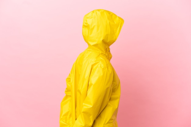 Young latin woman wearing a rainproof coat over isolated background in back position and looking back
