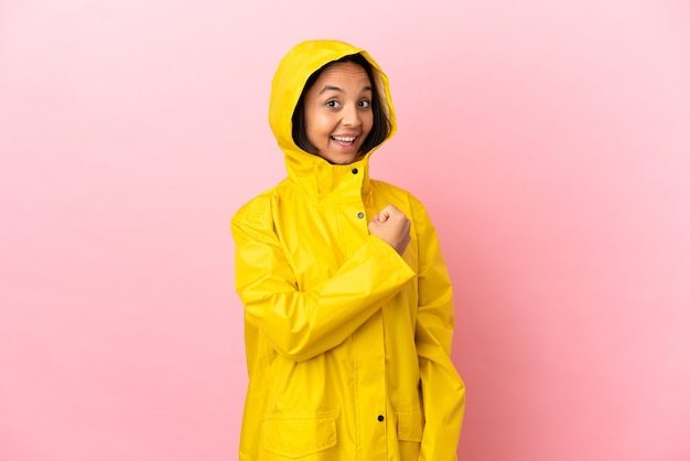 Young latin woman wearing a rainproof coat over isolated background celebrating a victory