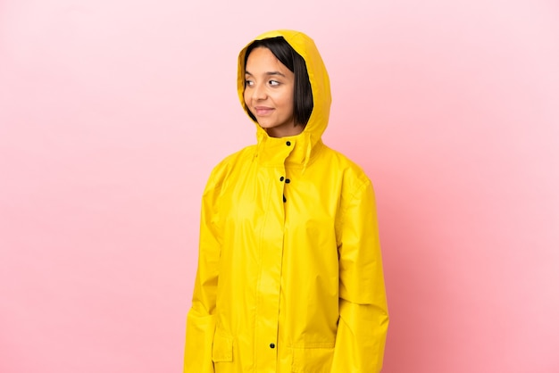 Young latin woman wearing a rainproof coat over isolated background having doubts while looking side