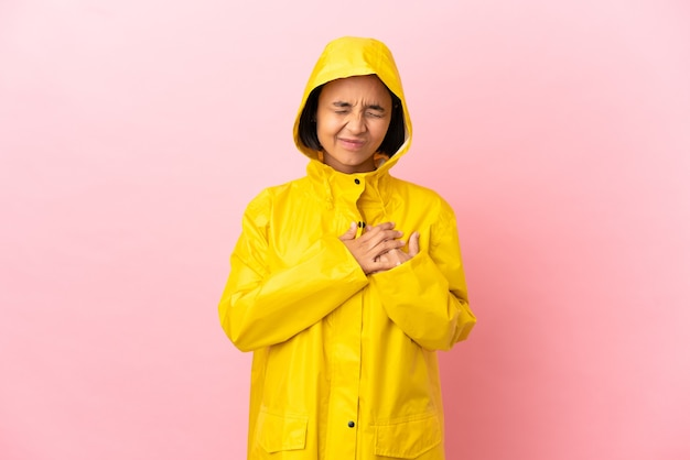 Young latin woman wearing a rainproof coat over isolated background having a pain in the heart