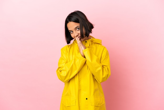 Young latin woman wearing a rainproof coat over isolated background keeps palm together. person asks for something
