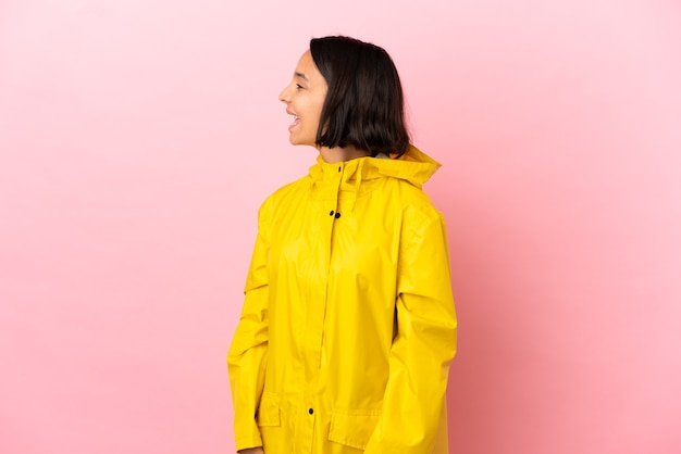 Young latin woman wearing a rainproof coat over isolated background laughing in lateral position
