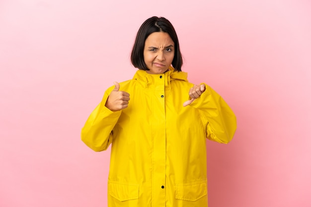 Young latin woman wearing a rainproof coat over isolated background making good-bad sign. undecided between yes or not