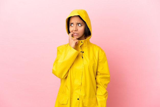 Young latin woman wearing a rainproof coat over isolated background nervous and scared