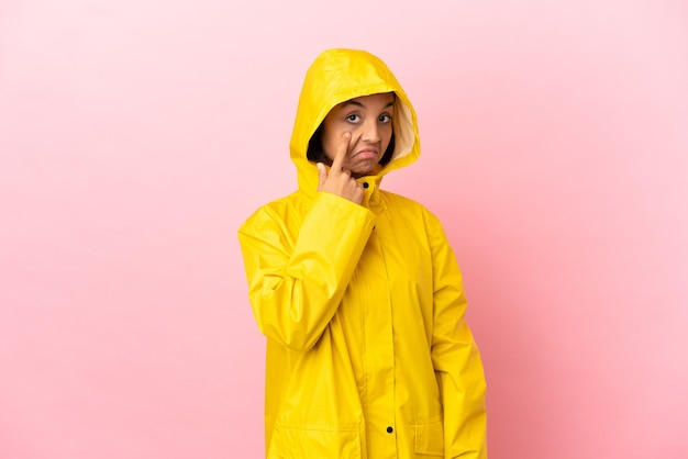 Young latin woman wearing a rainproof coat over isolated background showing something