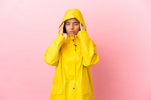 Young latin woman wearing a rainproof coat over isolated background with headache