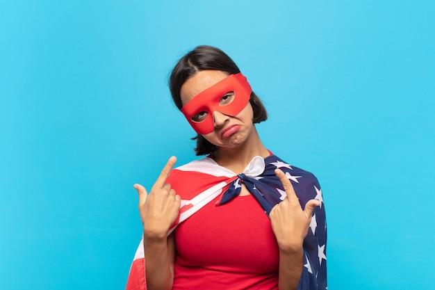 Молодая латинская женщина с плохим отношением выглядит гордо и агрессивно, указывая вверх или весело жестикулируя руками