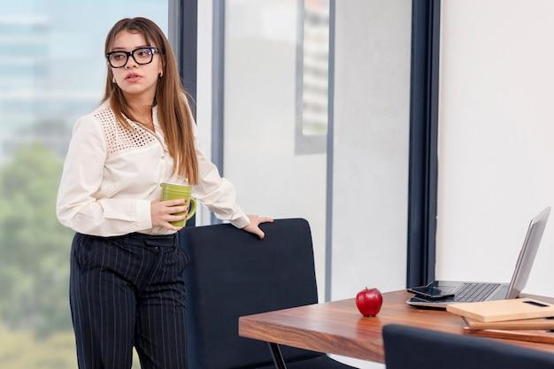 집에서 일하는 동안 휴식을 취하는 손에 커피 한 잔을 들고 있는 젊은 라틴 여성