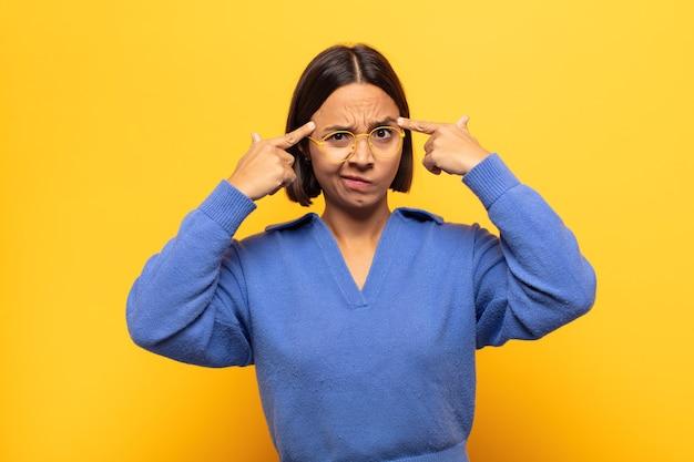 Молодая латинская женщина с серьезным и сосредоточенным взглядом, мозговой штурм и размышления над сложной проблемой