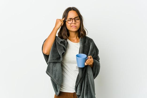 白い背景に分離された毛布を持つ若いラテン女性は、人差し指を頭に向けたまま、タスクに焦点を当てました。