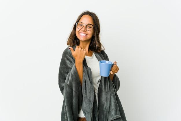 白い壁に隔離された毛布を持つ若いラテン女性は、両方の親指を上げて、笑顔で自信を持っています。