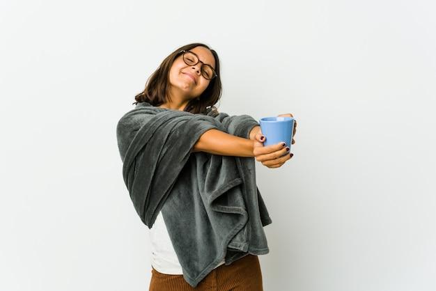 팔, 편안한 위치를 스트레칭 흰 벽에 고립 된 담요와 젊은 라틴 여자.
